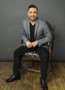 Photo of a man with dark hair and subtle beard, sitting in a chair. He is dressed in a gray jacket with a black shirt and black pants. His hands meet casually in front of his waist and he is smiling.