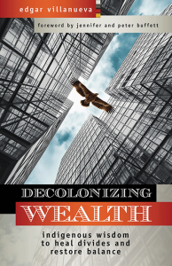Image of the book cover for Decolonizing Wealth. A large bird soars between skyscrapers; our view is looking up at the sky and bird from below. Subtitle: Indigenous wisdom to heal divides and restore balance.